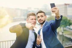 2 красивых бизнесмена говоря selfie Стоковая Фотография