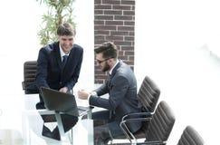 2 красивых бизнесмена обсуждая контракт в современном конференц-зале Стоковые Фотографии RF