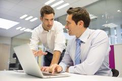 2 красивых бизнесмена работая совместно на компьтер-книжке в  Стоковое Изображение