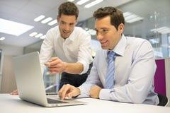2 красивых бизнесмена работая совместно на проекте в  Стоковые Фото