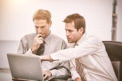 2 красивых бизнесмена работая совместно на проекте сидя на таблице Стоковые Изображения RF