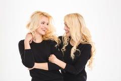 2 красивых близнеца сестер смотря один другого и усмехаться Стоковые Изображения RF