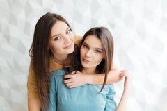 2 красивых близнеца сестер стоя и обнимая совместно Стоковые Фотографии RF