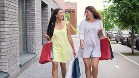 2 красивых девушки идут вниз с улицы с пакетами в их руках после ходить по магазинам, имеющ хорошее настроение 4K видеоматериал