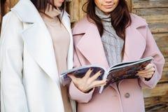 2 красивых девушки прочитали кассету и улыбку outdoors Стоковая Фотография RF