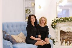 2 красивых девушки сестер представляя с улыбкой и сидя togeth Стоковые Изображения RF