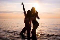 2 красивых девушки, студенты танцуют на пляже на розовом s стоковое изображение