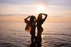 2 красивых девушки, студенты танцуют на пляже на розовом s стоковая фотография rf