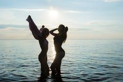 2 красивых девушки танцуют на пляже на backg моря захода солнца стоковая фотография rf