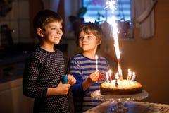 2 красивых дет, маленькие мальчики preschool празднуя день рождения и дуя свечи Стоковое Фото