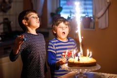 2 красивых дет, маленькие мальчики preschool празднуя день рождения и дуя свечи Стоковое Изображение RF