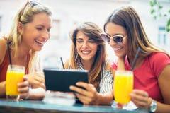 3 красивых друз в кафе используя ПК таблетки Стоковое фото RF