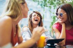 3 красивых друз в кафе используя ПК таблетки Стоковое Фото
