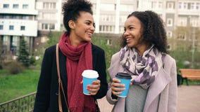 2 красивых друз женщины смешанных гонки выпивают кофе и беседы после ходя по магазинам и идя улицы города Стоковая Фотография RF
