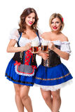 2 красивых девушки белокурых и брюнет oktoberfest глиняной кружки пива Стоковое Изображение RF