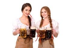 2 красивых девушки белокурых и брюнет oktoberfest глиняной кружки пива Стоковая Фотография RF