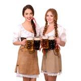 2 красивых девушки белокурых и брюнет oktoberfest глиняной кружки пива Стоковые Фотографии RF