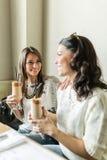 2 красивых девушки выпивая кофе и усмехаться Стоковые Фотографии RF