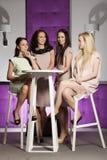 4 красивых девушки в костюмах стиля моды нося Стоковое фото RF