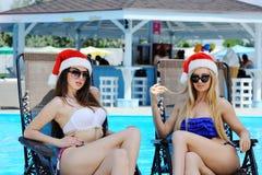 2 красивых девушки в красных крышках Санта Клауса на предпосылке бассейна Стоковая Фотография RF