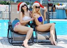 2 красивых девушки в красных крышках Санта Клауса на предпосылке бассейна Стоковое Изображение RF