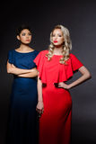 2 красивых девушки в платьях вечера представляя над серой предпосылкой Стоковые Изображения