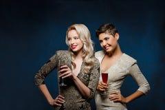2 красивых девушки в платьях вечера усмехаться, держа бокалы Стоковая Фотография