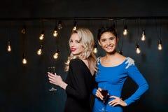 2 красивых девушки в платьях вечера усмехаться, держа бокалы Стоковые Изображения