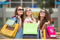 3 красивых девушки в солнечных очках с покупками Стоковая Фотография RF