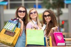 3 красивых девушки в солнечных очках с покупками Стоковые Фотографии RF