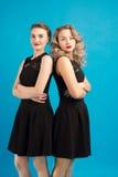 2 красивых девушки в таком же черном платье Стоковые Фотографии RF