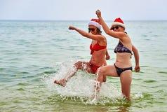2 красивых девушки в шляпе Санты рождества на пляже Стоковая Фотография