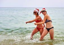 2 красивых девушки в шляпе Санты рождества на пляже Стоковое Изображение RF