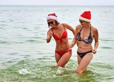 2 красивых девушки в шляпе Санты рождества на пляже Стоковое фото RF