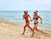 2 красивых девушки в шляпе Санты рождества на пляже Стоковые Изображения