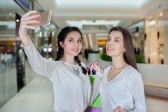 2 красивых девушки делают selfie в торговом центре Стоковые Фотографии RF