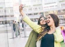 2 красивых девушки делая покупки в центре города и такине Стоковые Изображения RF