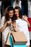 2 красивых девушки делая покупки, смотря телефон в моле Стоковые Фотографии RF