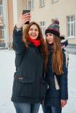 2 красивых девушки делая selfie на белой предпосылке Стоковые Фото