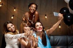 4 красивых девушки делая selfie на партии Стоковое Изображение RF