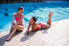 2 красивых девушки принимая selfie рядом с бассейном Стоковые Изображения