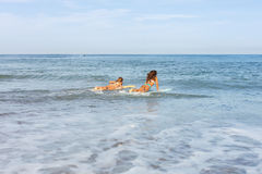 2 красивых девушки серфера на пляже идут в воду Стоковые Изображения