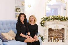 2 красивых девушки сестер представляя с улыбкой и сидя togeth Стоковые Изображения