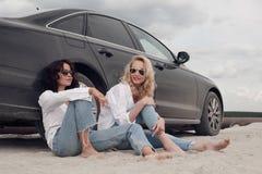 2 красивых девушки сидя на машине на пляже Стоковое фото RF