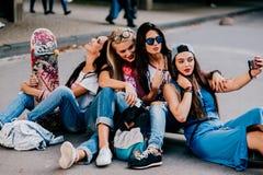 4 красивых девушки сидя на дороге Стоковое Изображение RF