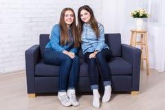 2 красивых девушки сидя на софе в живущей комнате Стоковые Изображения RF
