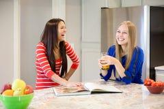 2 красивых девушки смеясь над и говоря в кухне Стоковые Фотографии RF