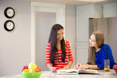 2 красивых девушки смеясь над и говоря в кухне Стоковое Изображение RF