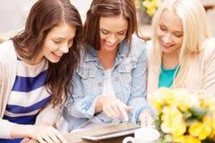 3 красивых девушки смотря ПК таблетки в кафе Стоковое Фото