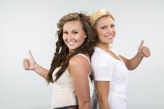 2 красивых девушки с большими пальцами руки вверх Стоковая Фотография